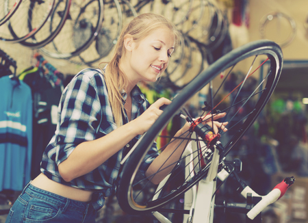 Young woman master is fixing wheel of city-bike in bicycle service