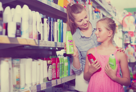 positive female with daughter holding conditioner for hair at the shop