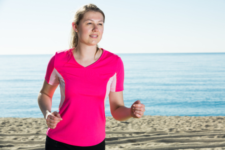 Young sporty woman running on ocean beach in sunny morning