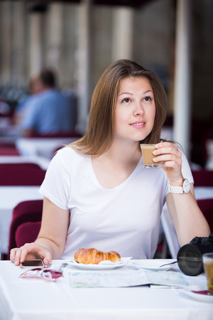 Young woman tourist is drinking coffee and chatting in the phone.