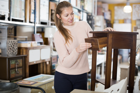 Positive woman customer choosing bedside in the furniture shop
