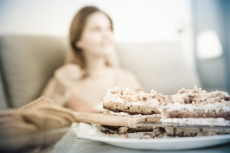 Positive woman sitting on sofa with plate with fresh cake