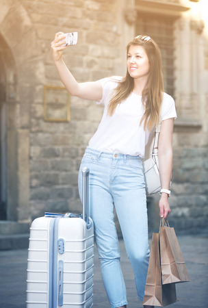 Positive young woman traveler with luggage doing selfie on vacation Stock Photo