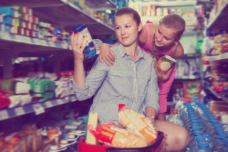 Glad mother with girl choosing rice with product basket