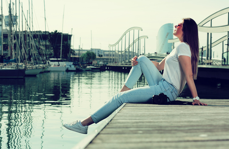 Portrait of young woman which is relaxing at pier in spring day.