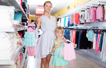 Smiling adult mother with little daughter holding wear for children Stock Photo