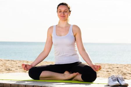 Smiling woman doing yoga training cross-legged on beach on sunny day Stock Photo