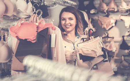 Happy cheerful positive female shopper boasting her purchases in underwear shop Stock Photo