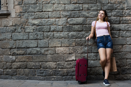 Traveling joyful girl standing with suitcases on stone wall background Stock Photo