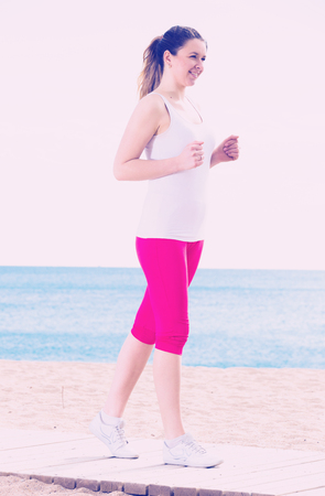 Young fit woman running on beach in sunny morning Stock Photo