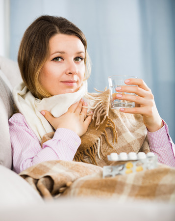 Young ill woman taking medicine to get better at home Stock Photo