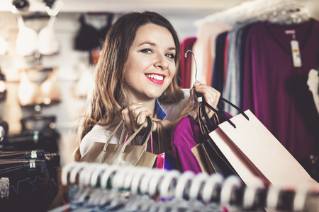 Positive female shopper boasting her purchases in underwear shop