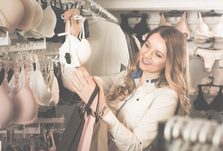 Pretty woman shopper examining bras in underwear shop