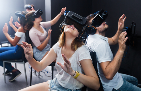 Young happy people having fun with new technology vr headset goggles
