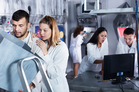Group of adults in a play trying to get out of escape room stylized under a laboratory