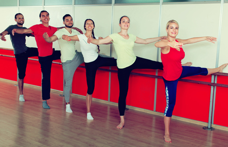 Group of happy spanish men and women practicing at the ballet barre