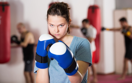 Young woman practicing different kiks in the boxing hall