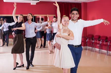Adult dancing couples enjoying latin dances in modern studio