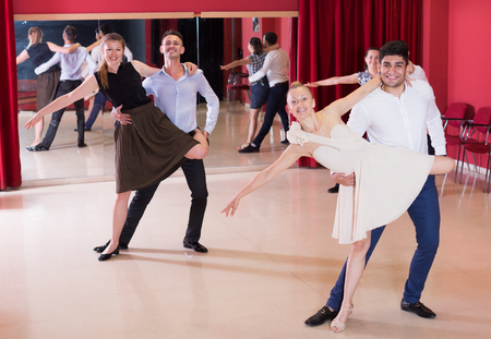 Young positive people dancing samba in pairs in dance hall