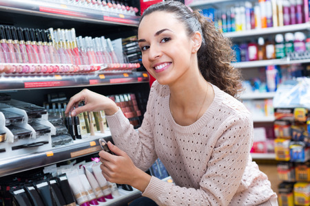 Smiling female customer selecting beauty treatment in makeup section