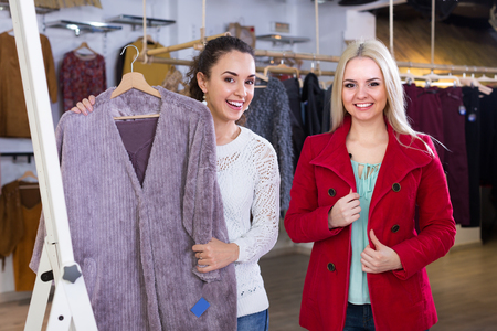 Ordinary young women shopping winter outwear at the apparel shop Archivio Fotografico