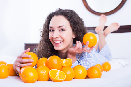 Portrait of pretty woman with sweet oranges in bed