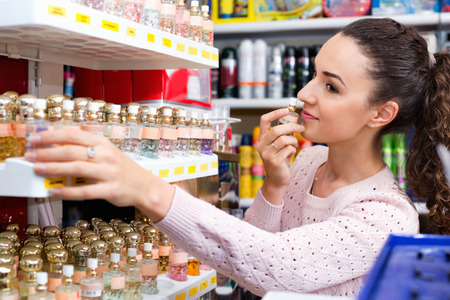Cheerful young beautiful woman choosing fragrance on display and smiling