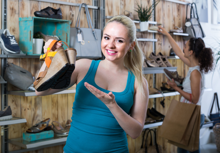 Young cheerful girl showing a chosen pair of shoes while her friend still choosing in shop