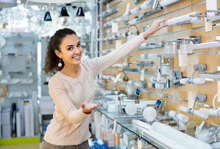 positive young russian  woman doing shopping in lighting shop