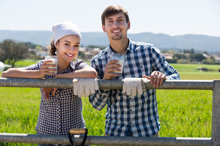 Portrait of young man and woman taking a pause and holding glass with milk