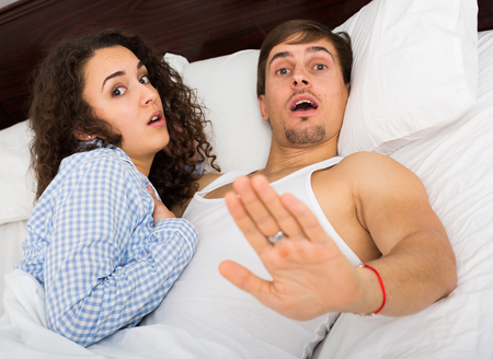 Frightened young people caught at adultery in family bed