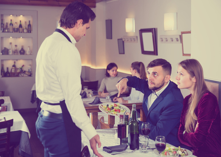 displeased guests conflicting with waiter because of poor quality of dish in restaurant