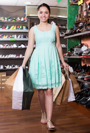 Young woman is going out of the shop with full hands of purchases