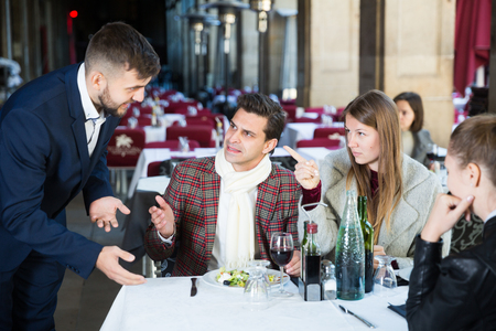 Dissatisfied people expressing displeasure with food and bad service to restaurant manager
