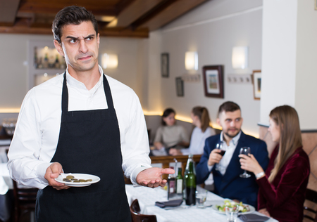 Portrait of waiter dissatisfied with small tip from cafe visitors