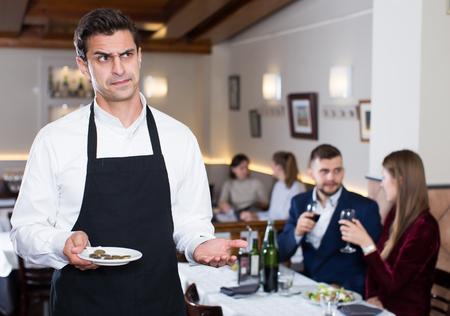 Ritratto di cameriere insoddisfatto della mancia dei visitatori dei caffè