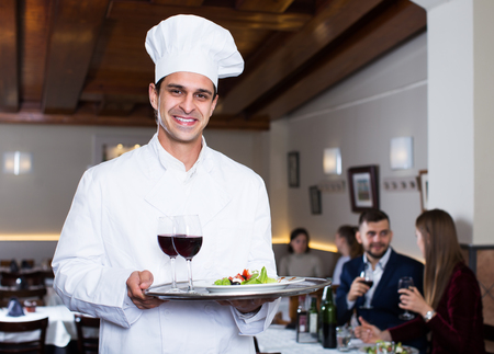 Portrait of handsome male chef with serving tray welcoming to restaurant Stok Fotoğraf