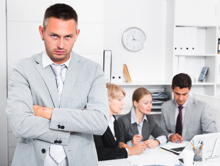 Business team tensely solving problems in office with upset man foreground