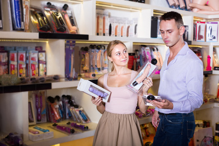 young adult couple selecting erotic toys in sex shop