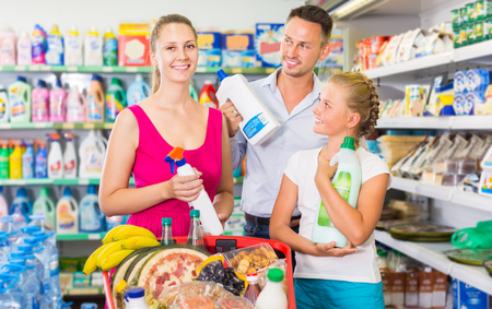 Portrait of smiling people showing household goods purchase in the domestic shop