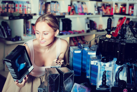 Portrait of joyful smiling young woman choosing toys for erotic games in sex shop  Imagens