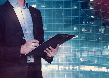 Respectable young businessman signing documents on background with blurred skyscraper Stock Photo