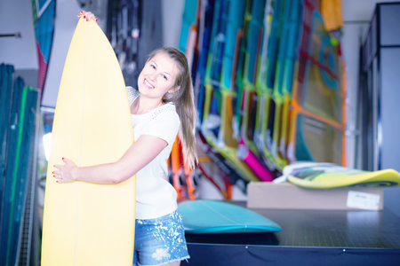 Young happy cheerful positive woman is posing with surfboard in store on the beach. Stock Photo