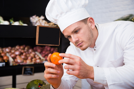 Young concentrated male cook choosing fruits in grocery shop Stock Photo