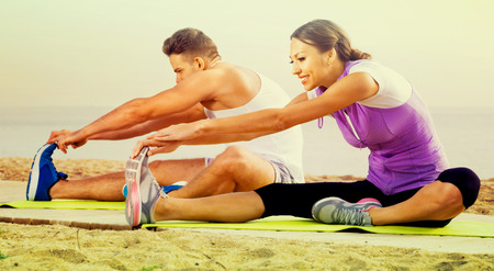 Positive smiling couple do exercises on beach by ocean at daytime