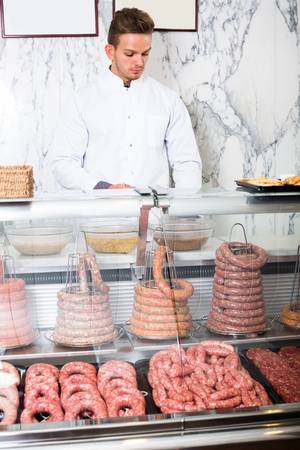 Glad adult ordinary man seller working at meat market Stock Photo