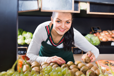 Young female shop assistant sorting kiwis in grocery shop