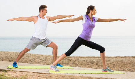 Man and woman training on beach by sea on sunny morning