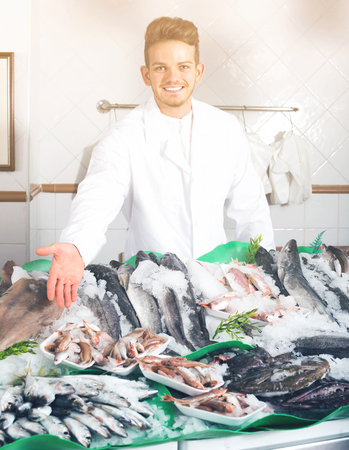 Happy guy selling chilled fish and seafood in store