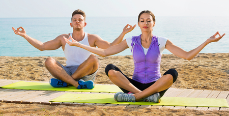 Charming  woman and man sitting cross-legged do yoga poses on beach at daytime Stock Photo